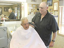 SUSAN MATHENY - Barber Charlie Campbell chats with customer Bob Turner as Campbell trims Turner's hair during a busy day Friday, at OK Barber Shop. Campbell has sold the business, but is continuing to work part time.