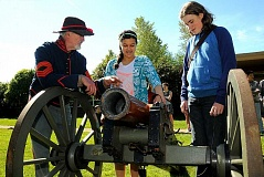 REVIEW PHOTO: VERN UYETAKE - Visitor Craig Flynn instructs Lake Oswego Junior High School students Malaika Murphy (left) and Adrian Edwards on how to fire a civil war cannon.