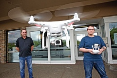 TIMES PHOTO: JAIME VALDEZ - Kenneth Silverton watches Drones Plus co-worker, Chris Griggs, fly a Phantom 3 drone at the business at Beaverton Town Square.