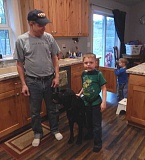 GAZETTE FILE PHOTO: BARBARA SHERMAN - Under Scott McDonald's supervision, his 6-year-old son John walks through their Sherwood home attached to his autism service dog Kai while little brother Wesley plays in the background.