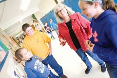 KEVIN SPERL - Cecil Sly fourth-grade teacher Gretchen Stack cannot walk the hallways of the school without being stopped by students to talk. Here, she visits with, from left, Kynsie Ramos, Rhett Kriege, and, on the right, Abby McNary, all fifth-graders.