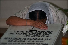 PHOTO BY KRISTIN SCHULTZ - Photographer Kristin Schultz said that she was stunned by the devotion of the attendees at a Mass at the Mother Theresa House in Calcutta, India. It was there she took this photo of a woman mourning at the gravestone of Mother Theresa. The woman was hugging the gravestone and sobbing.