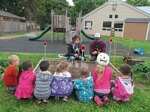 PHOTO BY ELLEN SPITALERI - Matthew Brown, right, deomstrates how to plant a seedling to assistant teacher Erika Garcia, and a group of 3, 4 and 5-year-old students at Oregon City View Manor Head Start Center.