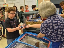 REVIEW PHOTO: VERN UYETAKE - River Grove student Kevin McDowell gets an ice cream bar at the snack cart during his schools fifth-grade tour of Lakeridge Junior High.