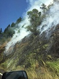 TODD HOLDER - Smoke pours off the hillside as the June 10 fire spreads through the dry grass.