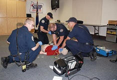COURTESY: TVF&R - Tualatin Valley Fire & Rescue firefighters from Station 67 participate in a high-performance CPR training at the Howard Terpenning Recreation Complex. From left, Jesse Fitzpatrick provides direction as Ryan Robinson prepares medication, David Johnson performs chest compressions, and Ben Oberhelman checks for a pulse.