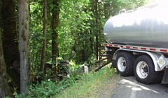 CLACKAMAS COUNTY SHERIFFS OFFICE - A tank trailer hangs over an embankment - still attached to the truck - after it jackknifed Wednesday afternoon at Brightwood, spilling hot asphalt into the Sandy River.