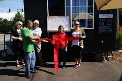 ANGELICA TRUE - Rafael Rojas (with scissors) handles the honors during a ceremonial ribbon cutting along with wife Marybel (second from right) and representatives from the Molalla Area Chamber of Commerce during Friday's grand opening of the 5 Tacos Taqueria cart.