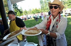 STAFF FILE PHOTOS: VERN UYETAKE - Lake Oswego Lion Club member Renee Kerr serves up pancakes at the annual pancake feed in George Rogers Park. The Lions will serve from 7 a.m.-noon.