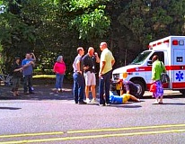 COURTESY OF KPTV-12 NEWS - Paramedics tend to the most recent bicyclist struck down at S.E. 26th Avenue at Powell Boulevard. As in the previous cases, a vehicle turning left from 26th struck a bicyclist proceeding with the green light.