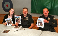 DAVID F. ASHTON - Co-authors Woodmere Elementary teacher Molly Thoman Walker and PPB Youth Services Division Officer Dave Thoman autograph the new Police Bureau childrens book, along with new Portland Police Bureau Chief Lawrence ODea III.