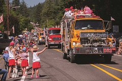 OUTLOOK PHOTO: JOSH KULLA - Children wave to a passing fire engine Saturday during the Corbett Fourth of July Parade.   6. The Corbett Parade attracted thousands of spectators to watch classic cars, rodeo queens, vintage military vehicles and much more.   7. Children rush to collect candy thrown from passing vehicles during the Corbett Fourth of July Parade.   8. Children look to catch candy thrown by this vintage military truck sponsored by the Weston familys auto dealerships.   9. The Corbett Fourth of July Parade is a festive occasion that includes vehicles of all stripes, including this 1948 Gibson Model D tractor.   10. The Weston fire engine cruises Springdale while showering candy on spectators at the Corbett Fourth of July Parade.   11. Throw Water, Not Candy was the motto of this float at the Corbett Fourth of July parade Saturday.