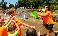 VERN UYETAKE - Angel McCoy of the Tree Hill Learning Center in Camas has fun throwing water on her camp group.