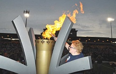 GARY ALLEN - Emily Wilson, a Special Olympics athlete from Multnomah County, officially kicked off the Summer State Games Saturday evening when she transferred the flame from the torch carried around the state to the giant version on Loran Douglas Field at Newberg High School. Wilson will compete at World Games this month in Los Angeles.