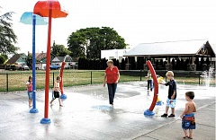 PEGGY SAVAGE - Molalla Mayor Debbie Rogge, center, cools off with kids at the Molalla Splash Pad. Rogge said she does not want to see the splash pad hours curtailed and encourages the adult community to conserve water.