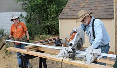 JASON CHANEY - Kathy Norrel of Colfax, Calif., (left) and Robert Garlett of Vancouver, Wash., cut siding while working on the Prineville house on Friday.