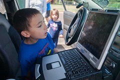 OUTLOOK PHOTO: JOSH KULLA - Benjamin Graham, 7, of Gresham, checks out a Gresham Police car at a recent Summer Kids In the Park (SKIP) session at Main City Park. His sister, Maddy, waits her turn in the background.