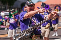 A member of The Beat Goes On marching band waves to the Summerfest crowd.