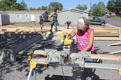 SUSAN MATHENY/MADRAS PIONEER - Isabella Allenbach, 18, saws lumbr for the framework of the first of six houses being built in Madras by the Youth Corps.