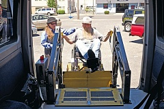 TRIBUNE PHOTO: JAIME VALDEZ  - Jeanette, a Radio Cab taxi driver, helps  Sarge, a Vietnam veteran, board her specially equipped taxi via the wheelchair lift.