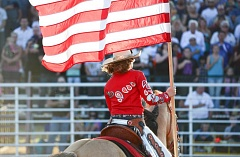 JOHN WILLIAM HOWARD - 2015 Columbia County Rodeo Queen Ashley Lanphear carries the American flag into the arena during opening ceremonies on Friday, July 24 at the Columbia County Fairgrounds.