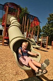 SPOKESMAN PHOTO: VERN UYETAKE - Cason Hill, 5, of Wilsonville enjoys going down the big slide in the newly reopened playground structure at Murase Plaza.