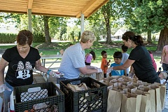 NEWS-TIMES PHOTO: CHASE ALLGOOD - From left to right, volunteers Susie Eggleston, Keri Wetzel and Shannon Holscher hand out lunches at Forest Groves Bard Park last Friday.