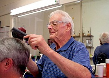 CONNECTION PHOTO: KELSEY O'HALLORAN - Ivan Tadic gives a haircut at his Multnomah Barber Shop. Oregon legislators recently declared June 26 'Ivan Tadic Day' in the barber's honor.
