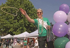 CONNECTION PHOTO: VERN UYETAKE - Michelle Cassinelli, owner of Village Bead, throws necklaces to the crowd.