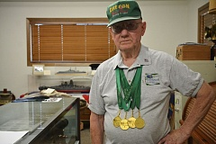 JOHN WILLIAM HOWARD - Scappoose resident Frank Weber, 91, wears all four of his gold medals won at the 2015 Washington State Senior Games on July 25. Weber's home is a treasure trove of Navy artifacts, where decades of naval history and 10 years of athletic success at senior games both local and national run together.