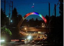 HILLSBORO TRIBUNE PHOTO: CHASE ALLGOOD - A rainbow of colorful lights is greeting pedestrians, drivers and MAX train passengers traveling through Hillsboro at night. Beginning at sunset and continuing through midnight, the city of Hillsboros Main Street Bridge is now home to a nightly display of public art, a light-emitting diode (LED) projector fades the colors into each other with slow light movement across the arch. The light show debuted Tuesday, July 21, 2015. The project will also reduce long-term maintenance costs associated with the replacement of the formerly blue light bulbs, which were already in need of replacement.