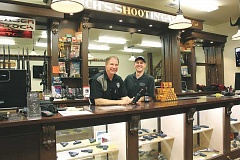 TYLER FRANCKE / WOODBURN INDEPENDENT - Proud owners - Father-son duo Lee and Kent Richeson smile at the counter of their store's new expansion wing, which was adorned in the style of an Old West saloon.