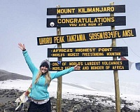 ELLE RENAULT PHOTO - Elle Renault posses in front of the sign that sits atop Mount Kilimanjaro. The 2015 Madras graduate climbed to the top of the 19,341-foot mountain last month on her senior trip.