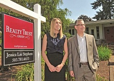 REVIEW PHOTO: VERN UYETAKE - Joe Menashe, managing principal broker for Realty Trust Group, and listing agent Jessica Lee Stephens pose outside a home for sale on Rainbow Drive in Lake Oswego. Menashe says the basic laws of supply and demand are driving the local market.