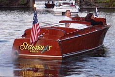 SUBMITTED PHOTOS - Mike Mayer and his wife, Nicole, are shown leaving the parade of boats at the Oswego Heritage Councils Collector Car & Classic Boat Show a few years ago. Mayer has had boats shown at the event for the past eight years.