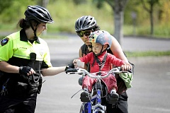TIMES PHOTO: JONATHAN HOUSE - Tigard Police officer April Keller gives Jamil Scamarone a sticker while he and his father watch the officers bike training at Cook Park.