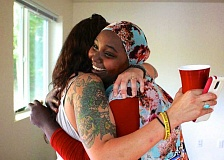 CONNECTION PHOTO: KELSEY O'HALLORAN - New Habitat for Humanity homeowner Fatiya Abdukarim (right) embraces Amethy Sandstrom, who volunteered to help build homes at the Hillsdale site.