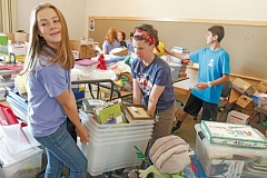 TIMES PHOTO: JONATHAN HOUSE - Teen volunteer Meredith Williams and librarian Samantha Wikstrom haul books during a cleanup event at the Tualatin Library.