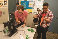 OUTLOOK PHOTO: JOSH KULLA - David Perry of OpenFab PDX demonstrates a 3D printer while Lyndsey Runyan, the Rockwood Library's creative spaces learning coordinator, examines a plastic violin Perry printed himself.