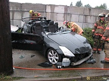 PORTLAND FIRE & RESCUE/DICK HARRIS - Firefighters examine the crashed vehicle after removing its top and driver's door.