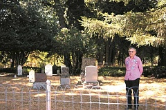 ANGELICA TRUE - Patricia Niday in Molalla's historic cemetery following the completion of erecting a new fence to protect the property. Niday and her family have repaired tombstones and cleaned up the cemetery as a volunteer project over the last six years.