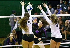 TRIBUNE PHOTO: JAIME VALDEZ - Portland Pilots outside hitter Emily Liger (10) strikes the ball between the arms of Portland State Vikings blockers Sarah Liva (15) and Pati Anae (9) Wednesday night at Stott Center.
