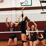 DAN BROOD - Sherwood High School sophomore Maddy Carbo (front) looks to get the ball past Tualatin's Grace Phillips (12) and Emiy Friesen (6) during Monday's match. The Lady Bowmen won in four sets.