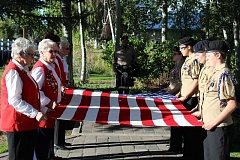 JASON CHANEY - American Legion Auxiliary members and NJROTC cadets fold the American flag.