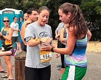 DAVID F. ASHTON - Brenna Archibald takes the Archibald Trotters wristband from her twin, Jenna Archibald, at the Johnson Creek/Springwater Trail exchange point for the Hood To Coast relay this year.