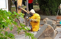 DAVID F. ASHTON - A Northwest Natural worker, dressed in an anti-static bunny suit, hops down into the excavated hole to make the repairs to the broken gas pipe.