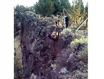 PHOTO BY ANGIE JEPPSEN - A high-angle rope rescue team from Crooked River Ranch Fire and Rescue loads an injured teen into a basket and pulls him up out of the Crooked River Canyon.