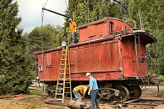 DAVID F. ASHTON - Riggers prepare the caboose to be lifted.