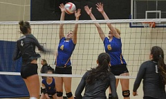 PHOTO COURTESY OF HEATHER FRASER - Laura Fraser (left) and Jennifer McCallister go up for a block against Jesuit during pool play at the South Albany State Preview Tournament, which was held on Saturday. The Cowgirls reached the gold bracket at the tournament, but lost in the quarterfinal round.