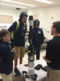 PHOTO COURTESY: KYLE LAIER - Garrett Diaz of MCAM Northwest shows a Hexagon metrology portable measuring arm to Bryce Hiatt, Spencer Park and Trey Henson.